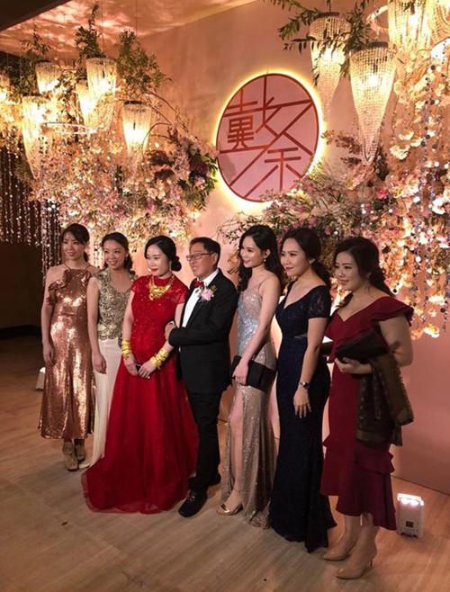 Cô dâu (váy đỏ) đứng bênchú rể chụp ảnh cùng khách mời đám cưới.