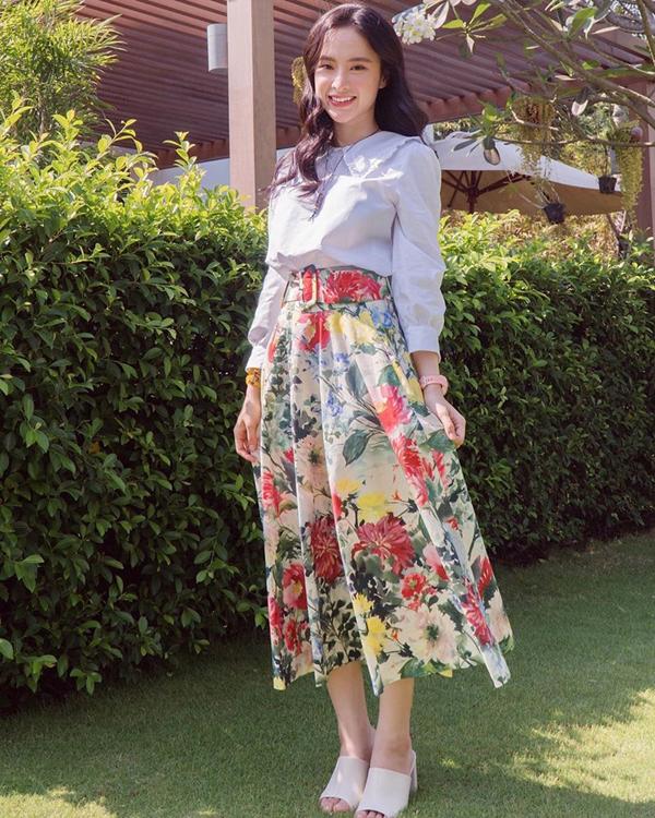 Angela Phương Trinh với hình ảnh nhu mì trong thiết kế áo sơ mi cổ cánh bướm. Trang phục đi kèm là chân váy midi dáng cổ điển, đi kèm đai lưng vải bản lớn.