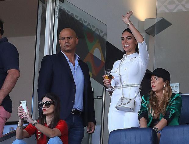 Georgina Rodriguez tươi tắn trong bộ đồ trắng vẫy tay với C. Ronaldo trước khi trận đấu bắt đầu.
