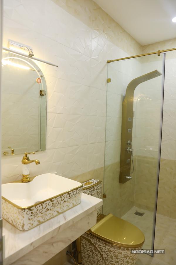 Phòng tắm với bồn rửa mặt, toilet, vòi sen đều mạ vàng nhìn rất sang trọng, bắt mắt.