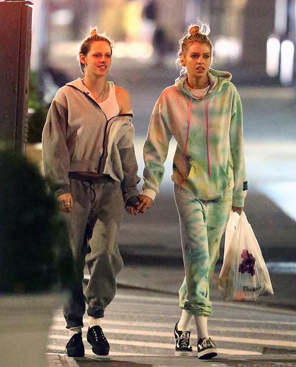 Kristen Stewart và Stella Maxwell lang thang tản bộ trong đêm. Hai người đẹp đều buộc túm tóc, để mặt mộc.