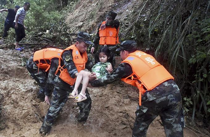 Đội cứu hộ Trung Quốcgiải cứu một em bé ra khỏi khu vực bị lấp trong bùn đất. Ảnh: AP.