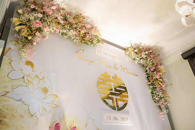 Các hoạ tiết truyền thống như chữ hỷ, đoá sen được thiết kế mang sự hiện đại, thanh lịch.Để tăng sự sang trọng, ekip còn phủ sơn màu vàng đồng lên lá monsterra - loại lá phụ trợ phổ biến trong trang trí cưới hiện đại.