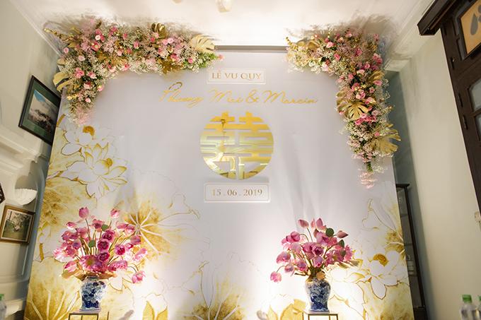 Không gian tại nhà cô dâu đượctrang trí có nhiều nét tương đồng với lễ ăn hỏi, mang đậm sắc màu cổ truyền, gợi nhắc gốc gác của cô dâu Hà thành. Tuy nhiên, bảng màu của không gian có chút thay đổi bao gồm màu: trắng, vàng đồng và hồng cánh sen.