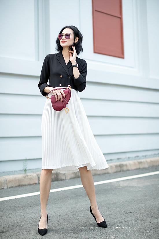 Phối hợp cùng sơ mi biến tấu cổ vest là phần chân váy xếp ly trên chất liệu chiffon lụa. Tông màu tương phản được bố trí hợp lý để mang tới nét thanh nhã cho tổng thể.