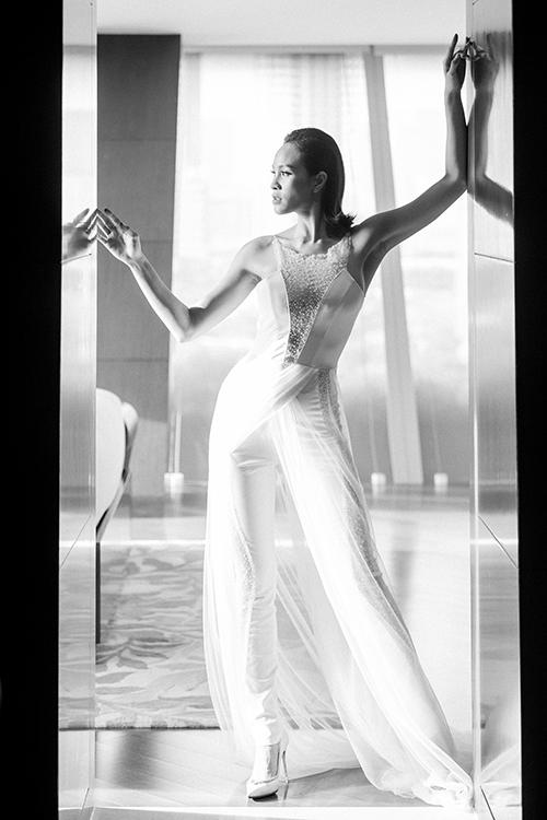 Bộ jumpsuit được kết hợp với những lớp voan trắng để hoàn thiện nên vẻ ngoài của cô dâu Phương Mai. Ở thiết kế này, phần cut out cùng những viên cườm được đính kết tỉ mỉ được chọn lựa làm điểm nhấn, vừa tôn cá tính mà vẫn làm toát lên vẻ nữ tính, gợi cảm đặc trưng của Phương Mai.