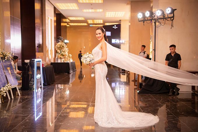 Đầm cưới chính mang phom dáng đuôi cácủa Phương Mai được Lek Chi đầu tư nhiều công sức và tâm huyết nhất trong 3 thiết kế. Bộ váy được thực hiện trong vòng 260 giờ bởi thợ may, thợ đính kết lành nghề. Điểm nhấn ở trang phục là chiếc áo choàng từ voan ren dài tới 3m tựa đôi cánh lộng lẫy của thiên thần.