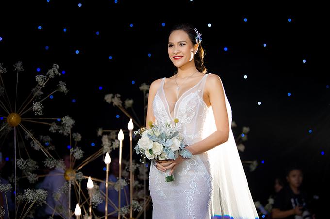 Thiết kế có cổ chữ V xẻ ngực sâu với đường bo tuyn trong suốt được kết hợp với họa tiết đối xứng, dải hoa leo bay bổng, mềm mại mang đến vẻ đẹp cổ điển, sang trọng và phá cách cho cô dâu.