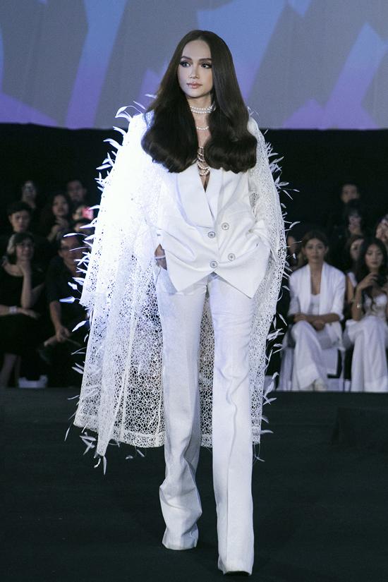 Hoa hậu Hương Giang diện suit và áo choàng kết lông vũ khi đảm nhiệm vedette cho màn 2.