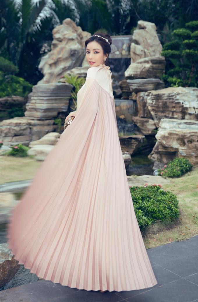 Xuất hiện sớm tại sự kiện, Lam Cúcthu hút sự chú ývớiđầm tone hồng nude xếp ly, form dáng áo choàng capequyền lực. Hoa hậu bớitóccao kết hợp phụ kiện, make up ton-sur-ton với trang phục.