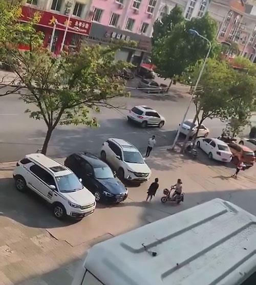 Người vợ chạy ra trước mũi chiếc SUV màu trắng để ngăn chồng rời đi sau khi cãi nhau. Ảnh: AsiaWire.