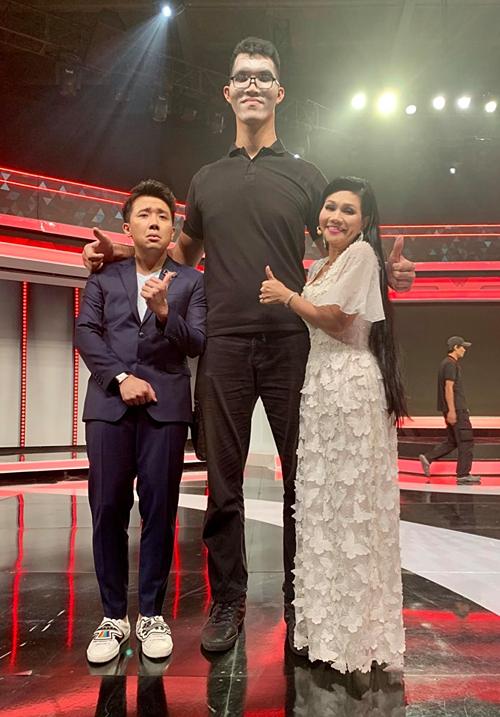 Đuông dừa gặp cây dừa, MC Trấn Thành dí dỏm bình luận về bức ảnh của mình khi đứng cạnh nam khách mời cao 2m2 trong một gameshow truyền hình.