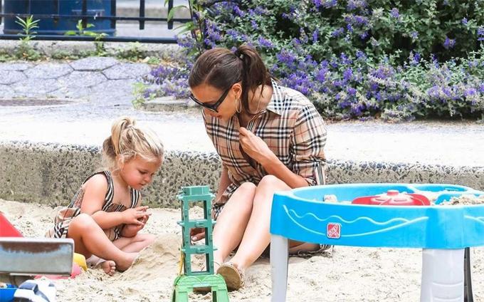Irina không ngại ngồi bệt trên cát chơi cùng con.
