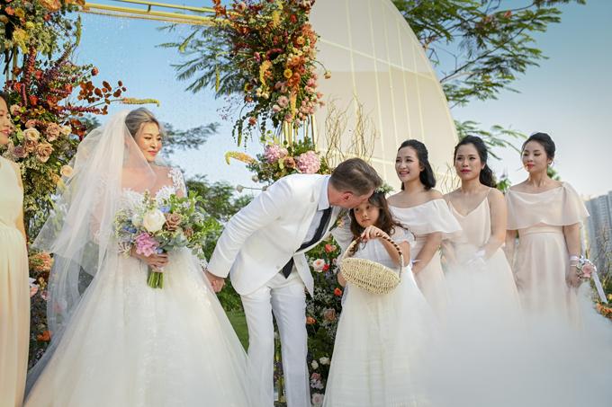 Chú rể dành nụ hôn trên trán cho con gái riêng của cô dâu.