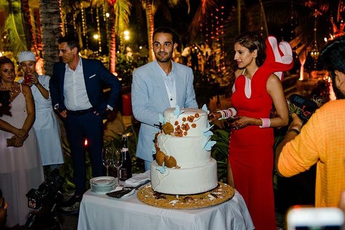 Cặp uyên ương cắt bánh cưới trước sự chứng kiến của gia đình, bạn bè và khách mời. Nghi lễ cắt bánh khởi đầu cho tiệc cưới sôi động diễn ra sau đó.