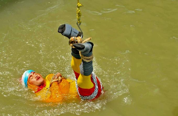 Chanchal Lahiri bị trói chặt bằng xích và dây thừng lúc được thả xuống sông Hằng để thực hiện màn ảo thuật hôm 16/6. Ảnh: AFP.