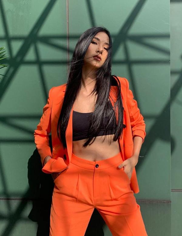 Với áo thun ôm body, kiểu crop-top được Hoàng Thùy chọn làm điểm nhấn cho bộ suit tông cam rực rỡ.
