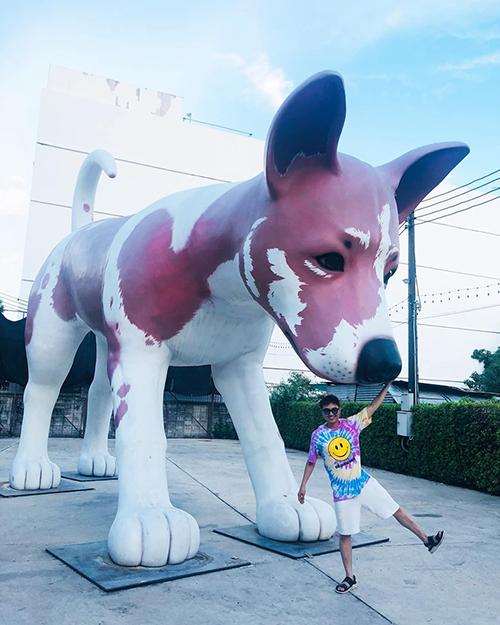 Thanh Duy pose hình với tượng chú chó khổng lồ tại công viên ChangChui Creative Park ở Thái Lan.