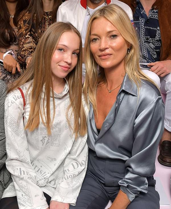 Siêu mẫu và con gái ngồi hàng ghế đầu xem show thời trang.