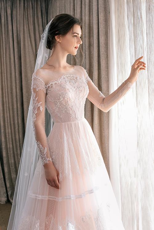 Đầm đính ren ở thân trên, có cổ illusion (cổ hai trong một), giúp cô dâu hóa thân thành nàng thơ yêu kiều.