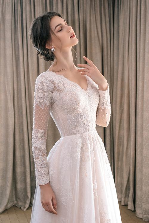 Chi tiết hoa ren làm tăng sự nữ tính, các hạt đá lấp lánh tạo độ bắt sáng cho thân váy. Đầm cưới cổ chữ V giúp nàng dâu khoe khéo khuôn ngực đầy gợi cảm.