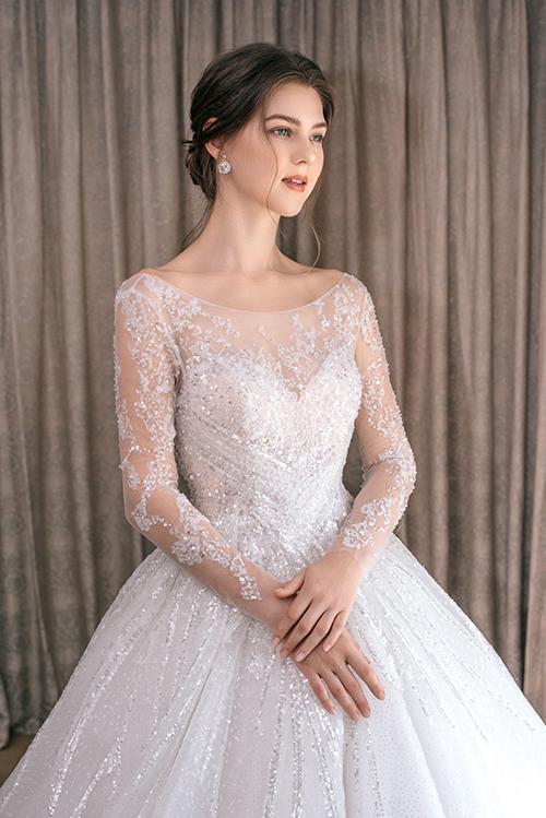 Họa tiết đăng đối trên nền váy được lấy cảm hứng từ chi tiết ren trên váy cưới của các công nương, công chúa hoàng gia châu Âu. Thiết kế có độ gợi cảm khi ôm trọn đường cong ở phần trên của cơ thể.