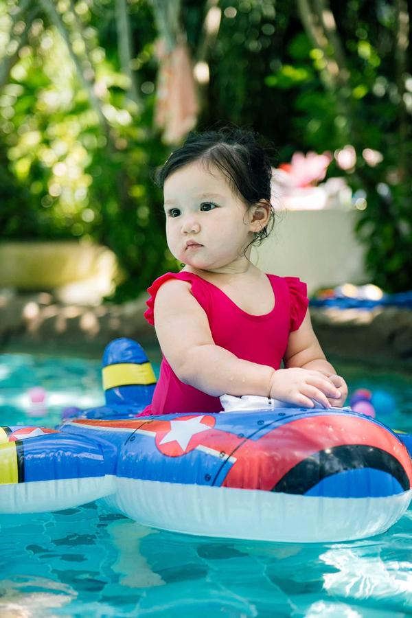 Nàng công chúa bé bỏng diện áo tắm điệu đà, vui đùa trong bể bơi.