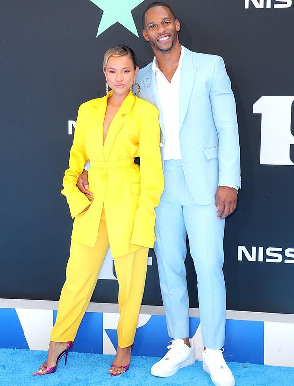 Karrueche Trần và bạn trai nổi bật trên thảm đỏ BET Award với trang phục vest một màu vàng và xanh. Cặp đôi chênh lệch về chiều cao nhưng vẫn gây ấn tượng bởi phong cách thời trang sành điệu.