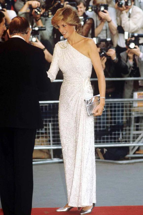 Luôn được coi là biểu tượng thời trang bất hủ của thế giới, Công nương Diana không đóng khung bản thân trong hình ảnh kín cổng cao tường, đúng chuẩn hoàng gia. Thay vào đó, bà thường xuyên có những lựa chọn phá cách, không ngại thử nghiệm các ý tưởng táo bạo và khéo léo diện đồ với khoảng hở chừng mực nhằm tôn lên vóc dáng săn chắc, gợi cảm.Tháng 6/1983, Diana tỏa sáng tại lễ ra mắt phim Octopussy với thiết kế lệch vai duyên dáng của Hachi. Trang phục này từng được bán ở mức hơn 60.000 bảng Anh (gần 1,8 tỷ đồng) trên sàn đấu giá Christies.