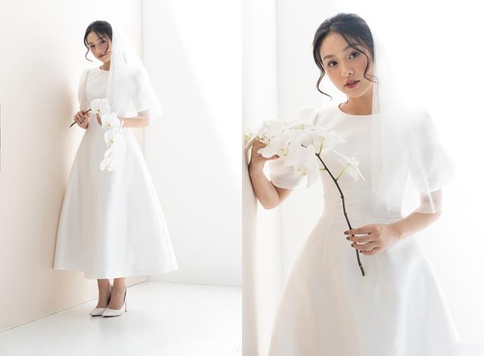 Sự quay trở lại của nhữngmẫu váy tối giản thập niên 1960là điềukhông thể phủ nhận trong xu hướng cưới hiện đại, đặc biệt là từ đám cưới của Meghan Markle. Mẫu đầm cổ tròn, dáng xòe được ra đời nhằm đáp ứng mong muốn về chiếc váy thanh lịch, tối giản của tân nương.Đầm tối giản không chú trọng vào đính kết mà tập trung xử lý chất liệu, phom dáng sao cho toát lên thần thái, cá tính riêng biệt của cô dâu, khiếnngười đối diện tập trung ánh nhìn vào tân nương.Trang phục: Lecia Bridal
