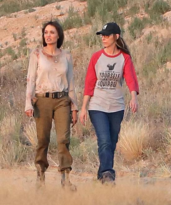 Jolie mặc chiếc áo bê bết máu cùng trợ lý trường quay tới địa điểm ghi hình.