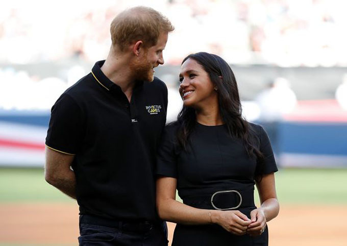 The couple gaze adoringly at each other as they step out onto the diamond