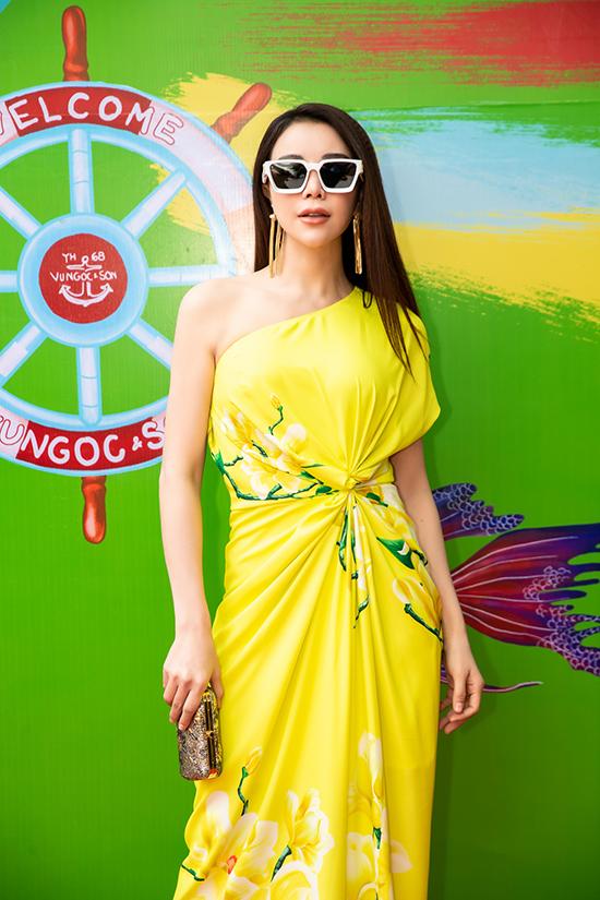 Trà Ngọc Hằng khoe vẻ đẹp gợi cảm với mẫu váy lệch vai thiết kế trên chất liệu vải in hoa văn bắt mắt.
