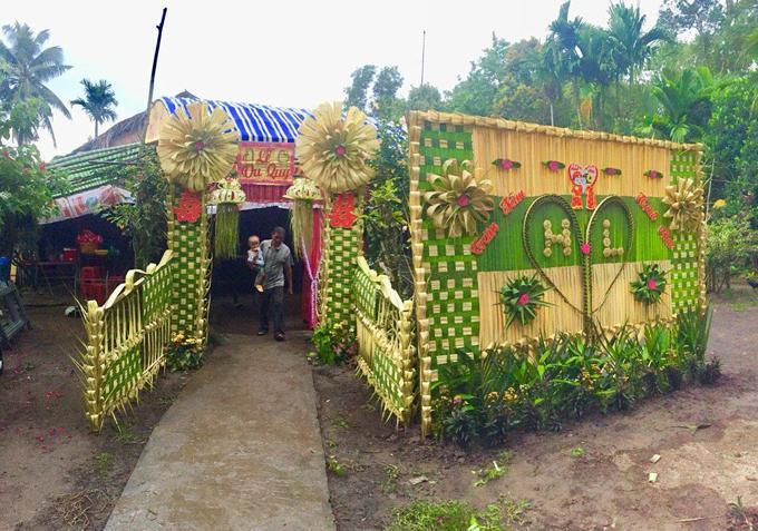 Vì yêu thích nét đẹp truyền thống nên cặp cô dâu chú rể không sử dụng cổng cưới hiện đại mà chọn lựa cổng cưới lá dừa.