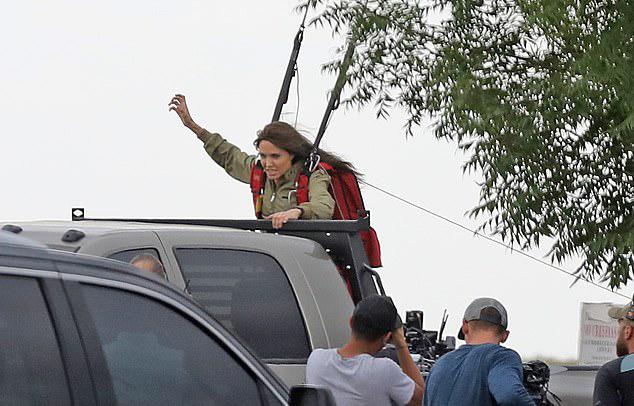 Nữ diễn viên được bảo vệ bằng dây cáp để đóng cảnh nhảy lên chiếc xe bán tải.