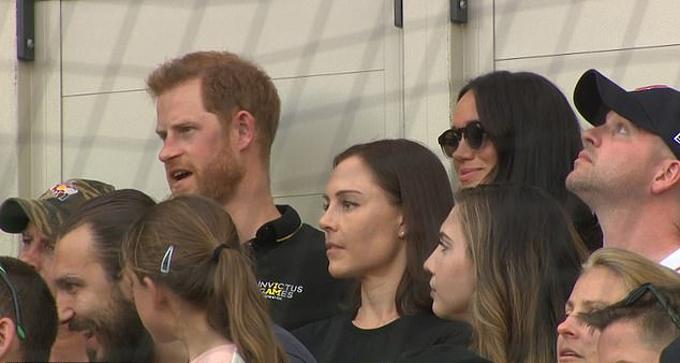 Hoàng tử Harry và vợ Meghan Markle hào hứng theo doi trận bóng chày hôm 29/6. Ảnh: UK Press.