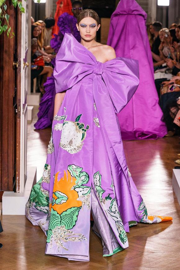 Cũng tham gia trình diễn cho Valentino, siêu mẫu thế hệ mới Gigi Hadid diện bộ đầm tím suông rộng với điểm nhấn là chiếc nơ bản lớn trước ngực.