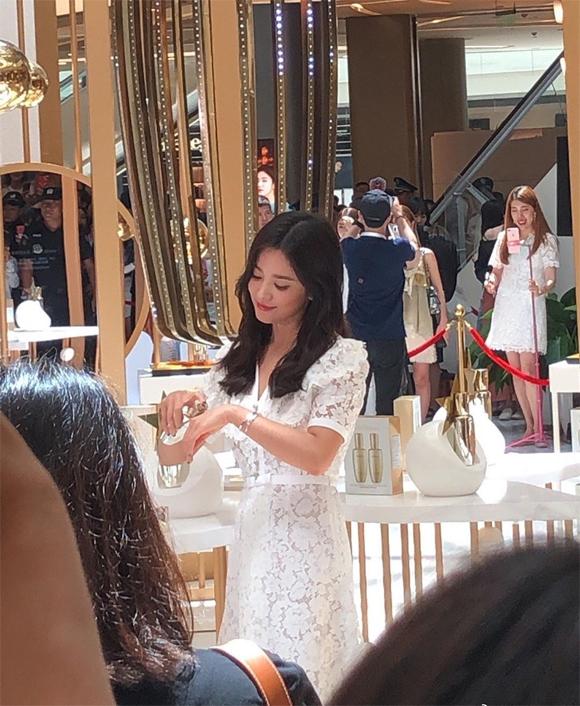 Song Hye Kyo thử mỹ phẩm tại sự kiện, khoe nhan sắc và làn da láng mịn.