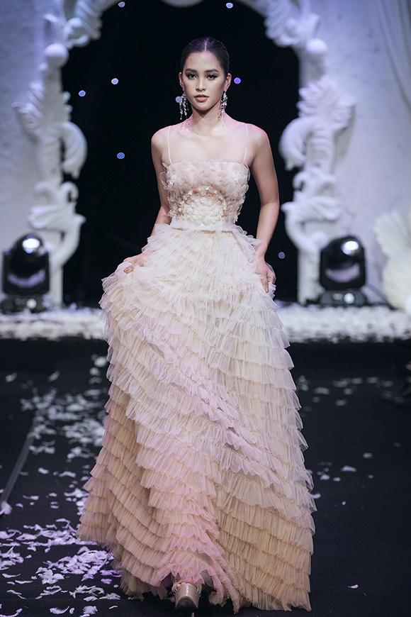 Trong chương trình, hoa hậu Việt Nam 2018 còn thể hiện một mẫu váy xếp tầng bồng bềnh màu pastel dịu nhẹ. Kinh nghiệm xuất hiện trên các sàn catwalk giúp cô hoàn thành tốt phần trình diễn và được khán giả cổ vũ nhiệt tình.
