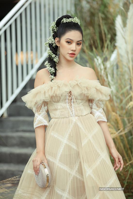 Jolie Nguyễn điệu đà cùng váy trễ vai và làm tóc cầu kỳ đi sự kiện.