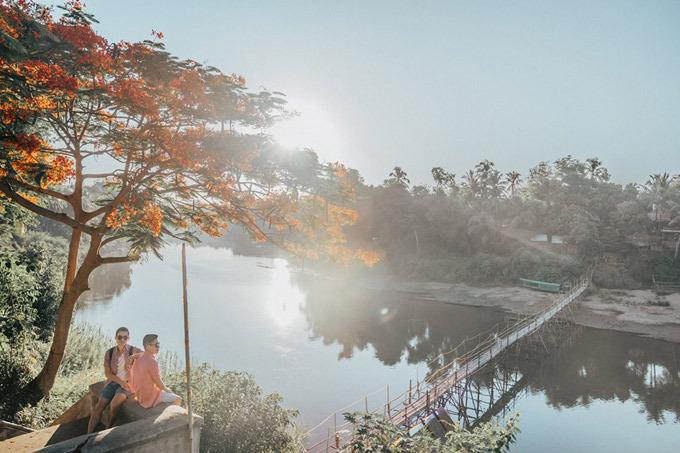 Luang Prabang là một bán đảo nằm giữa 2 con sông Mekong và Nam Khan. Adrian Anh Tuấn và bạn đời đã dậy từ 7h để chụp bình minh. Để băng ngang qua sông Nam Khan, người dân dựng2 cây cầu tre. Cầu này chỉ đi được 6 tháng màu khô, mùa mưa nước sông dâng cao khá nguy hiểm nên họ sẽ gỡ cầu bỏ đi, năm sau sẽ dựng lại. Để có chi phí xây cầu mỗi người đi qua phải trả 5.000 kip, khoảng 15.000 đồng. Bên kia cây cầu này là nhà hàng Dyen Sabai rất ngon và yên tĩnh, ngon tới nỗi hai người đã phải quay lại đây 2 lần.
