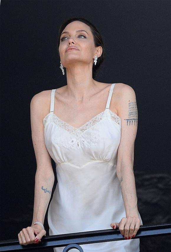 Nữ diễn viên quyến rũ với váy lụa hai dây, bông tai và vòng kim cương.
