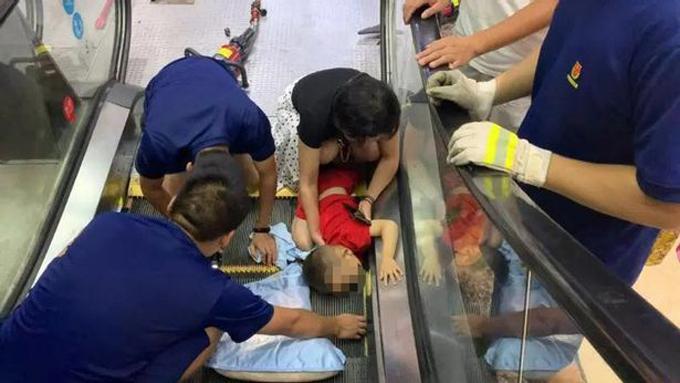 Bé trai 2 tuổi bị kẹp tay phải vào thang cuốn ở trung tâm thương mại City Star, thành phố Giang Nguyên, tỉnh Hồ Nam hôm 5/7. Ảnh: AsiaWire.