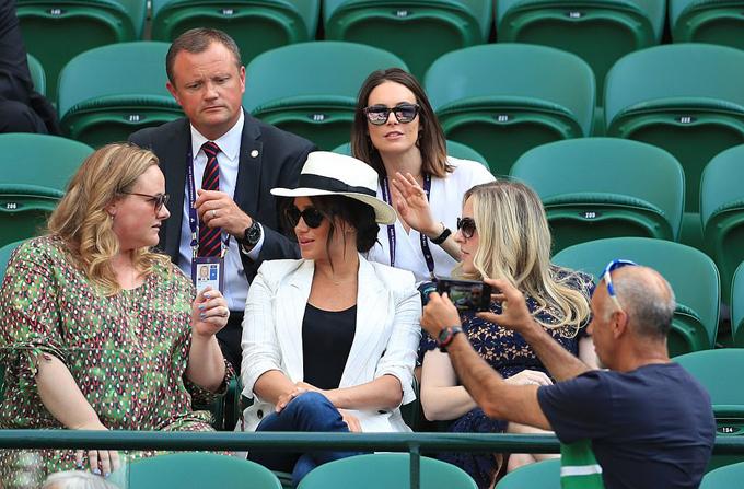 Một người đàn ông giơ máy ảnh chụp gần Nữ công tước xứ Sussex trên khán đài trận đấu giữa Serena Williams và Kaja Juvan trong khuôn khổ giải Đơn nữ Wimbledon hôm 4/7. Ảnh: PA.