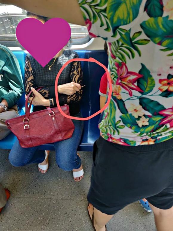 Người phụ nữ cầm tăm chĩa sang bé trai ngồi cạnh trên tàu điện ngầm ở Singapore tuần trước. Ảnh: Reddit.