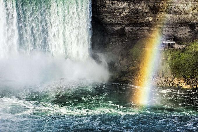 Người đàn ông được tìm thấy ngồi trên một hòn đá (phía bên phải) sau cú rơi từ thác Móng ngựa hôm 9/7. Ảnh: LightRocket.