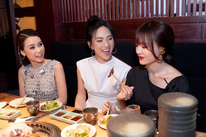 Các người đẹp vui vẻ trò chuyện và gắp thức ăn cho nhau.