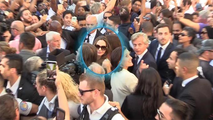 Angelina di chuyển khó khăn giữa biển người.