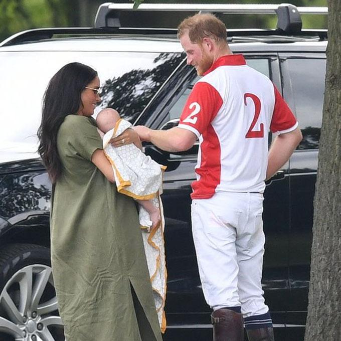 Bé Archie trông đáng yêu khi được quấn trong một chiếc khăn và nằm cuộn tròn trong vòng tay mẹ.  Meghan diện chiếc váy màu rêu dáng rộng che bụng lớn sau khi sinh. Trước khi trận đấu diễn ra, Harry tranh thủ trêu đùa, nựng má con trai.