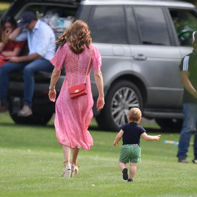 Hoàng tử Louis, 15 tháng tuổi, vui vẻ chạy trong sân cỏ, dưới sự giám sát của mẹ Kate. Bà mẹ ba con diện chiếc váy voan mềm màu hồng nữ tính, kết hợp đôi xuồng buộc dây trẻ trung.